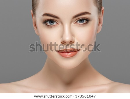 portrait of a beautiful young woman with perfect skin closeup on gray background  - stock photo