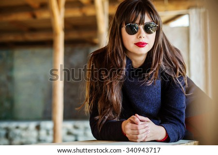 portrait of a beautiful young woman with red lips outdoors - stock photo
