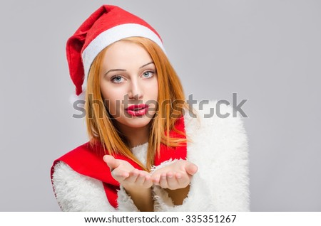 Portrait of a beautiful young woman with red Santa hat smiling blowing a kiss. Happy girl dressed for Christmas time. Merry Christmas. - stock photo
