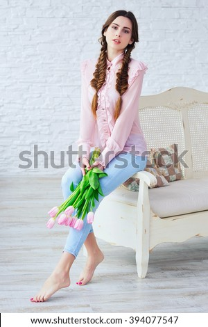 Portrait of a beautiful young woman with spring bouquet of pink tulips  - stock photo