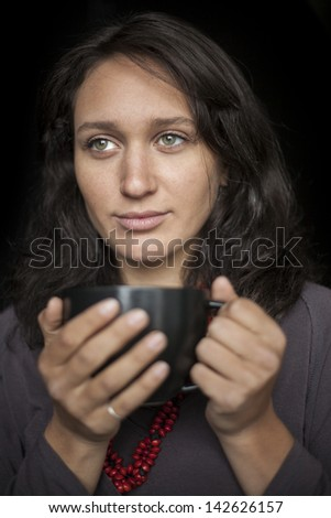 Portrait of a beautiful young woman with striking green eyes drinking coffee from a black cup. - stock photo