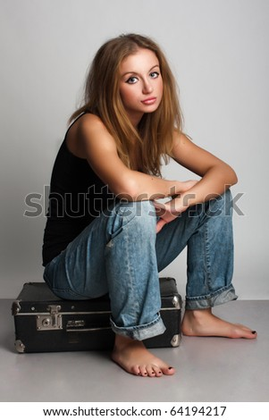 portrait of a beautiful young woman with suitcase - stock photo