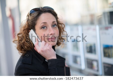 Portrait of a beautiful young women looking at real estate announcement - stock photo