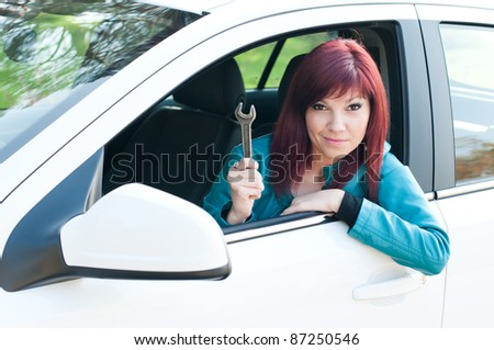 Portrait of a bewildered young woman sitting in a car outdoors with a wrench in her hand - stock photo