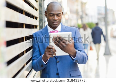 Portrait of a black businessman wearing suit looking at his tablet computer in urban background - stock photo