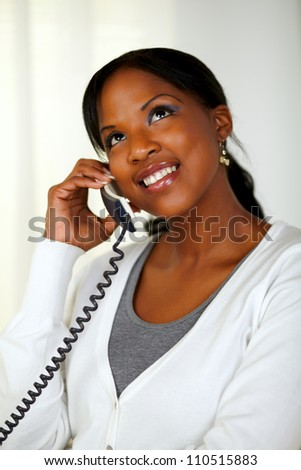 Portrait of a black woman looking up while talking on phone at soft colors composition - stock photo