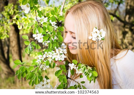 Portrait of a blond girl with blooming branch - stock photo