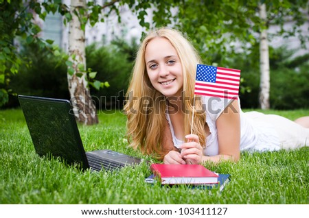 Portrait of a blond girl with USA flag on the grass with laptop - stock photo