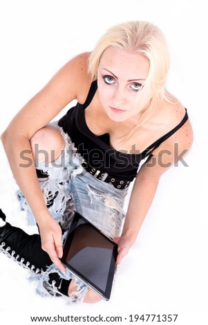 Portrait of a blonde alternative girl sitting on the ground holding a tablet PC. - stock photo