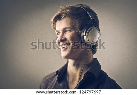 Portrait of a blonde guy listening to the music with headphones - stock photo