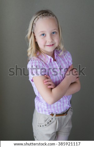 Portrait of a blonde little girl with blue eyes posing - stock photo