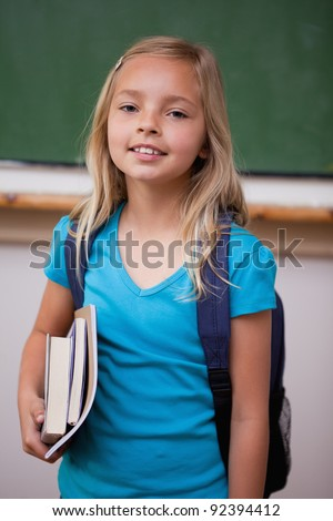 Portrait of a blonde schoolgirl holding her books in a classroom - stock photo