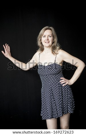 Portrait of a blonde woman in an attractive summer dress on a black background. - stock photo