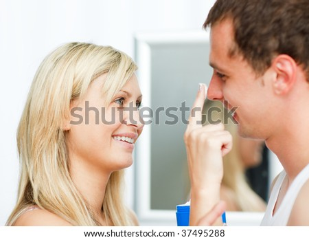 Portrait of a blonde woman putting cream on her boyfriend's nose in bathroom - stock photo