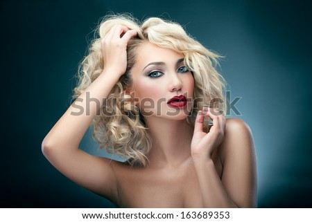Portrait of a blonde woman touching her hair - stock photo