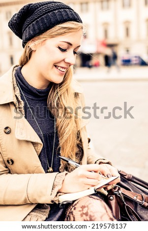 Portrait of a blonde woman writing diary - stock photo