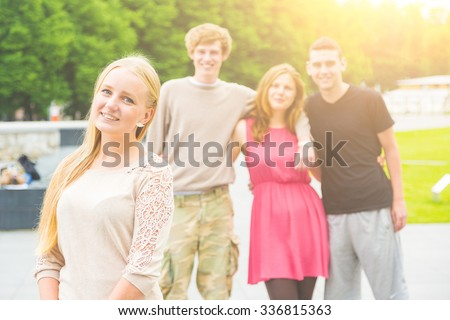 Portrait of a blonde young woman with a small group of friends on background. She is in her early twenties, smiling and looking at camera. Multiethnic group. Friendship and lifestyle concepts. - stock photo