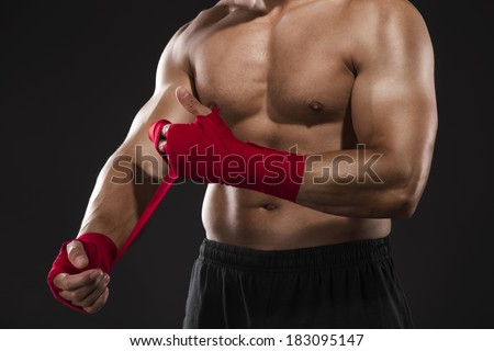 Portrait of a body combat athlet aplying tape on the hands - stock photo