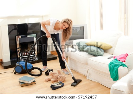 Portrait of a bored woman vacuuming at home - stock photo
