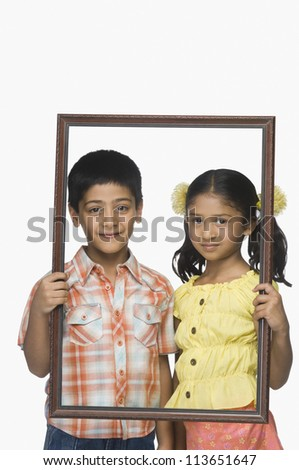 Portrait of a boy and a girl holding an empty picture frame - stock photo