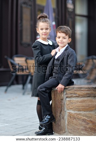 Portrait of a boy and a girl in school suit - stock photo