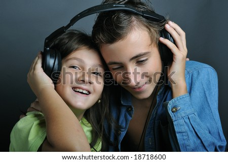 Portrait of a boy and a little girl listening music - stock photo