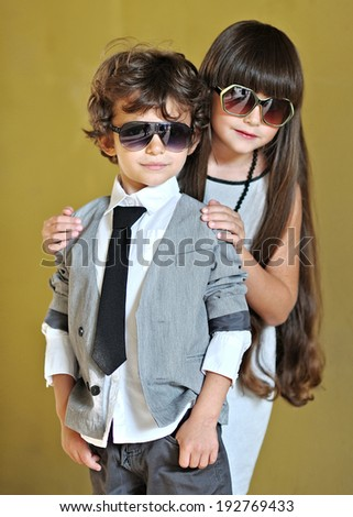 portrait of a boy and girl in stylish dress - stock photo
