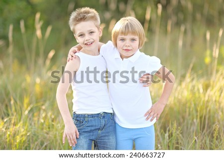 Portrait of a boy and girl on the meadow in summer - stock photo