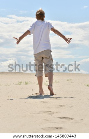 Portrait of a boy from the back walking barefoot in the sand - stock photo