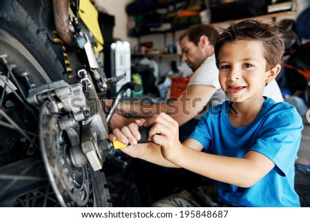 portrait of a boy helping his dad with fixing a motorcycle in the garage - stock photo