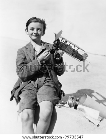 Portrait of a boy holding a model airplane and smiling - stock photo