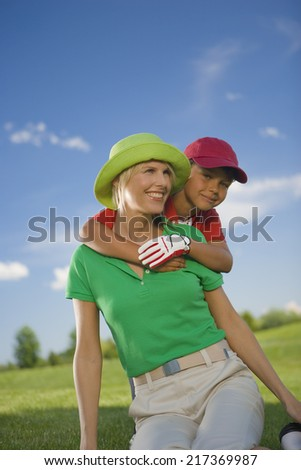 Portrait of a boy hugging his mother from behind - stock photo