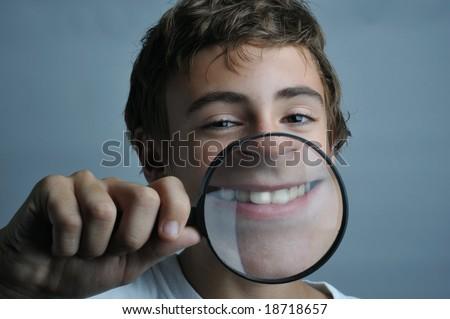 Portrait of a boy showing his dent through a magnifier - stock photo