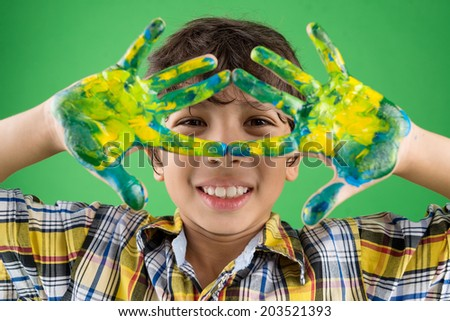Portrait of a boy showing his hands painted in different colors - stock photo