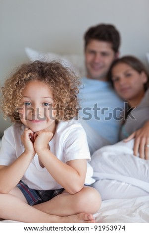 Portrait of a boy sitting on his parents's bed while looking at the camera - stock photo