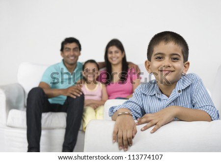 Portrait of a boy smiling with his family in the background - stock photo