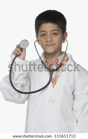 Portrait of a boy wearing lab coat and showing a stethoscope - stock photo