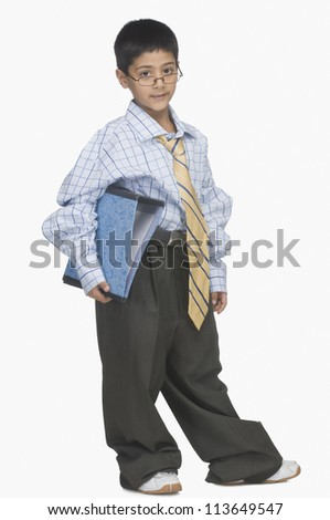Portrait of a boy wearing oversized clothes and holding a file - stock photo