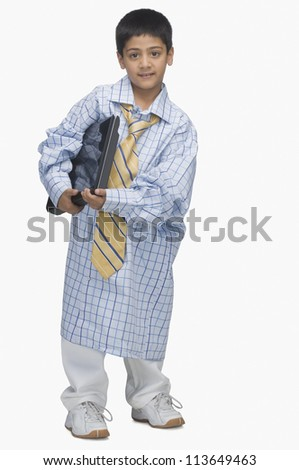 Portrait of a  boy wearing oversized shirt and holding a laptop - stock photo