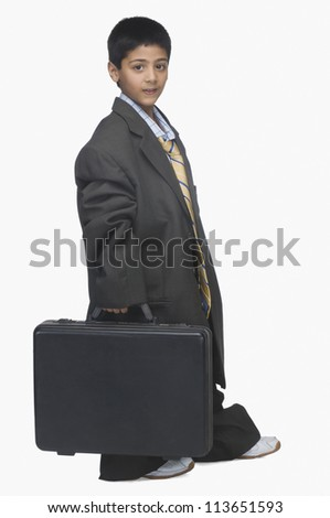 Portrait of a  boy wearing oversized suit and holding briefcase - stock photo