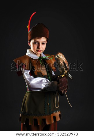 Portrait of a boy with a falcon bird in costumes of Robin Hood. For Halloween - stock photo