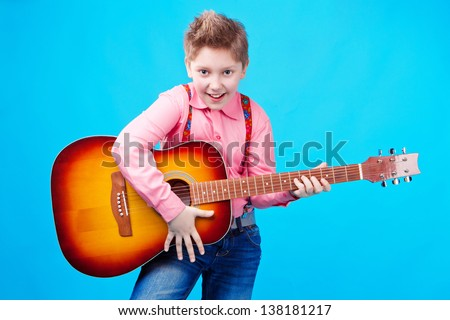 portrait of a boy with guitar on the blue background - stock photo