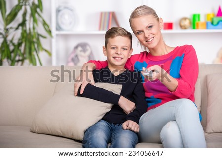Portrait of a boy with his mom are watching TV at home. - stock photo