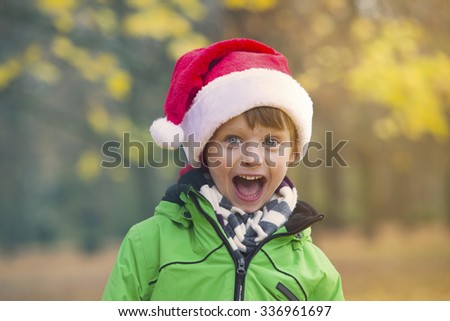 portrait of a boy with Santa hat in park in the fall - stock photo