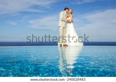 portrait of a bride and groom kissing on a infinity pool against the sky - stock photo