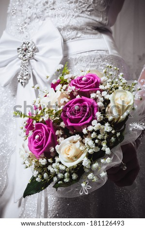 Portrait of a bride with flowers. young beautiful bride holding bouquet. wedding bouquet at bride's hands isolated on white. - stock photo