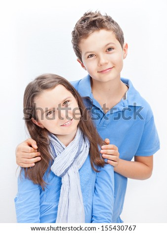 Portrait of a Brother and Sister, both wearing a blue shirt. - stock photo