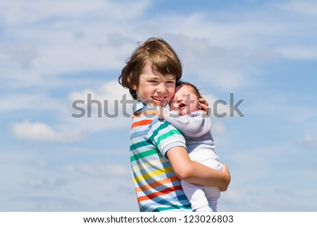 Portrait of a brother hugging his baby sister with a beautiful cloudy sky background - stock photo
