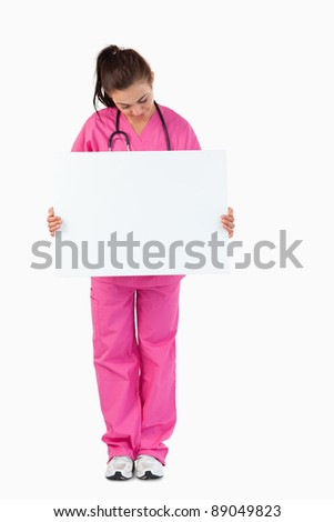 Portrait of a brunette doctor holding a blank panel against a white background - stock photo