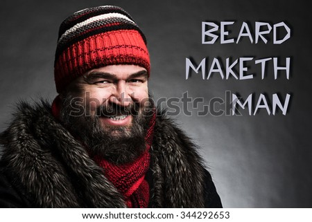 """Portrait of a brutal mature man clothed in winter clothes on a dark background with """"BEARD MAKETH MAN"""" text - stock photo"""